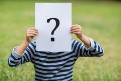 Chłopiec zakrywa jego twarz z plakatem który pokazuje znaka zapytania znaka Fotografia Royalty Free
