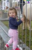 Ch?ri girl regarder Poney mignon zoo images libres de droits