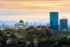 Ch?teau d'Osaka avec les fleurs de cerisier et le district des affaires de centre ? l'arri?re-plan ? Osaka, Japon photographie stock