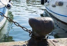Chaîne attachée sur une borne Corde d'amarrage enroulée autour du crampon sur le fond de mer Metal le cabestan dans le port pour  photos libres de droits