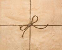 Chaîne de caractères attachée dans une proue sur un papier réutilisé brun Photographie stock libre de droits