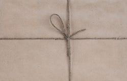 Chaîne de caractères attachée dans une proue sur un papier réutilisé brun Images libres de droits