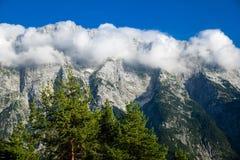 Chaîne de haute montagne avec des dessus couverts en nuages photographie stock