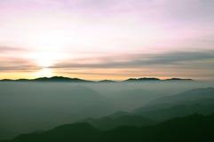 Chaîne de montagne de brouillard à l'aube Photographie stock
