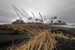Chaîne de montagne devant les dunes de sable noires image libre de droits