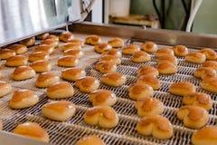 Chaîne de production de cuisson Biscuits sous la forme de coeurs après le revêtement de lustre sur le convoyeur Photographie stock