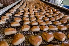 Chaîne de production de cuisson Biscuits sous la forme de coeurs après le revêtement de lustre sur le convoyeur Photos stock