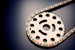 Chaîne de rouleau avec le pignon sur le fond foncé Il est employé sur des voitures, motos, bicyclettes et en industrie mécanique images stock