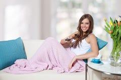 Chaîne de télévision changeante de belle jeune femme images stock