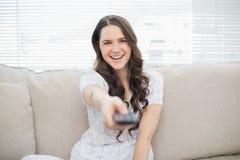 Chaîne de télévision changeante de sourire de jeune femme Photos stock