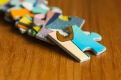 Chaîne des morceaux d'un puzzle sur une surface en bois Image stock