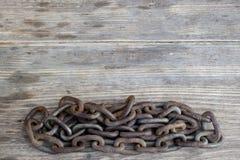 Chaîne en métal sur le vieux fond en bois gentil photographie stock