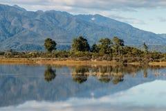 Chaînes de montagne dans les Alpes du sud réfléchissant sur le lac Photographie stock libre de droits