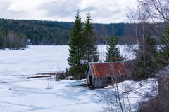 Chałupa blisko zamarzniętego jeziora zdjęcie stock