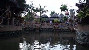 Chałupa domy wzdłuż spowodowany przez człowieka rzeki w parku tematycznym zdjęcie wideo