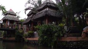 Chałupa domy wzdłuż spowodowany przez człowieka rzeki w parku tematycznym zbiory wideo