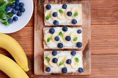 Chałupa ser, świezi banany i jagod kanapki z chrupiącym chlebem na drewnianej desce, Jarosz ściska przepis Odgórny widok Zdjęcie Stock