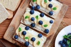 Chałupa ser, banany i jagod kanapki z chrupiącym chlebem na drewnianej desce, Wielki chałupa ser ściska przepis zbliżenie Zdjęcia Royalty Free