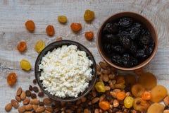 Chałupa ser w bielu talerzu i przycina w brown talerzu Przycina, suszył morele, wysuszone mandarynki i migdały na świetle wo Zdjęcia Stock