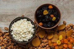 Chałupa ser w bielu talerzu i przycina w brown talerzu Przycina, suszył morele, wysuszone mandarynki i migdały na świetle wo Zdjęcie Stock