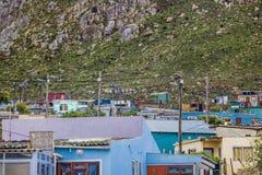 Chałupa stwarza ognisko domowe w społeczności miejskiej pod masywną górą w Kleinmond, Zachodni przylądek, Południowa Afryka zdjęcia royalty free