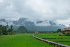 Chałupa w ziemi uprawnej i górze z mgłą Zdjęcia Stock