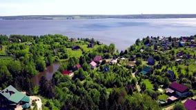 Chałupy miasteczko na tła błękita jeziorze klamerka Odgórny widok kraj wioska w lasowym terenie jeziorem zdjęcie wideo