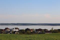 Chałupy na tle woda i niebo, w przedpolu zielona trawa Wioska Laporovichi, Zaslavskoe rezerwuar, Minsk Reg fotografia stock