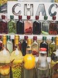 cha-cha-cha georgiano tradizionale della bevanda dell'alcool in bottiglie con differenti frutti ed erbe fotografia stock