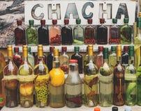 cha-cha-cha georgiano tradizionale della bevanda dell'alcool in bottiglie con i frutti e la vendita differenti delle erbe immagini stock libere da diritti