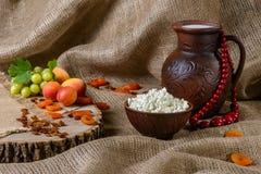 Chałupa ser w glinianym naczyniu, mleko, winogrono, morele na drewnianym tle Zdjęcia Royalty Free