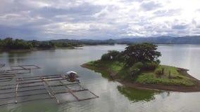 Chabola flotante, jaulas de los pescados empleadas el depósito eléctrico hidráulico de la presa del lago almacen de metraje de vídeo