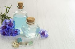 Chabrowa kwiat błękitne wody w szklanych butelkach i kąpielowej soli na białym drewnianym stołowym tle Istotny olej knapweed dla zdjęcia royalty free