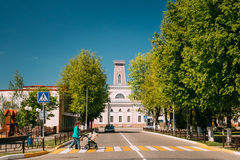 Chachersk, Belarus. Woman With A Stroller Crosses The Road On A Crossing. Old City Hall In Sunny Summer Day On Stock Image
