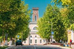 Chachersk, Wei?russland Leute, die auf Stra?e nahe alter Stadt Hall In Sunny Spring Day gehen Stadt Hall In Chechersk stockbild