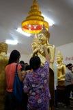 Chachoengsao, Таиланд - 7-ое августа 2010: Буддист положил листовое золото на Будду на висок Sothorn Стоковые Изображения