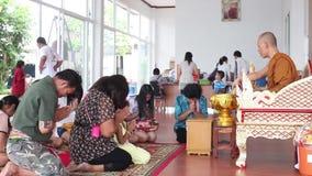 CHACHOENGSAO, TAILÂNDIA 4 DE JULHO DE 2012: A monge budista polvilha a água santamente em visitantes do templo em Chachoengsao em filme