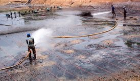 Cleaning the mud at the bottom of pond. CHACHOENGSAO THAILAND - JULY 13 : Unidentified men control high pressure water jet nozzle to clean the mud at the bottom stock photo