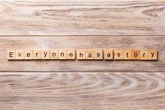 Chacun a un mot d'histoire écrit sur le bloc en bois Chacun a un texte d'histoire sur la table en bois pour votre desing, concept photo libre de droits