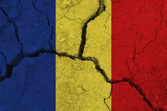 Chad flag on the cracked earth. National flag of Chad. Earthquake or drought concept stock photo