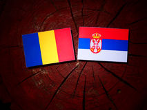 Chad flag with Serbian flag on a tree stump isolated. Chad flag with Serbian flag on a tree stump royalty free stock image