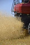 Chaff, dust, and straw leave a combine during harvest Royalty Free Stock Images