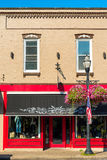 Chagrin Falls storefront. CHAGRIN FALLS, OH - JULY 30, 2017: A clothing storefront with a bright red facade and decorative awning adds to the charm of this royalty free stock images