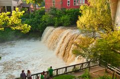 Chagrin Falls viewing platform. CHAGRIN FALLS, OH - JUNE 28, 2015: The viewing platform next to the falls is a popular gathering spot to see the water roar over royalty free stock images