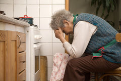 Chagrin of old woman by cooking. Senior royalty free stock image