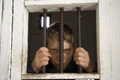 Chahuteur derrière les bars antiques de prison Photographie stock libre de droits