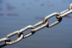 Chain. A close-up of a chain with blurry water on the background stock photography