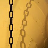 Chain. Black chain and yellow painted steel background Royalty Free Stock Photos