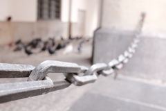 Chain. Abstract angle on an iron chain in an old building - selective focus is on the chain link on the left, copy space on the right Stock Image