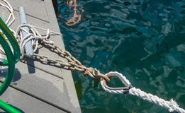 Chain attached to cleat on dock and dock tie up that is attached to a boat off camera - shown over deep water. A Chain attached to cleat on dock and dock tie up stock photography